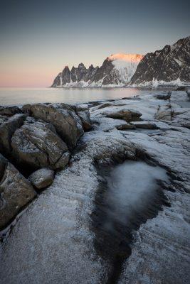 Photo verticale d'une plaque de glace gelée avec en fond les Dents du Diable au couché de soleil sur l'île de Senja